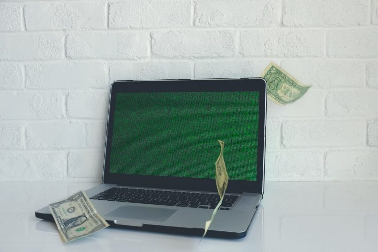 MacBook pro and and dollar bills